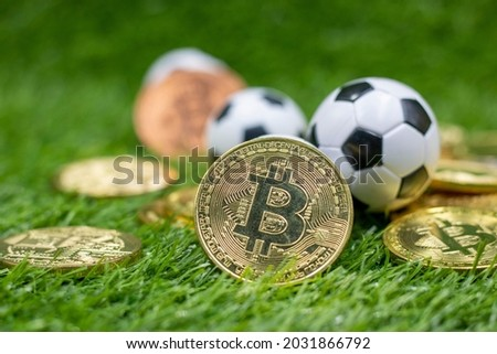 Bitcoin and Soccer Ball are on Green grass for gambling concept. Major Soccer Clubs in Europe Make it  as gateway into speculative cryptocurrency