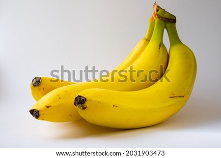 Three ripe yellow bananas against a white background. Healthy food, food product photography