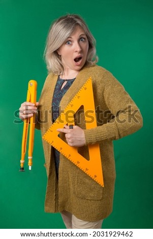 Adult woman posing with compasses and protractor. Photos on school subjects. Studio photo with chroma key background.