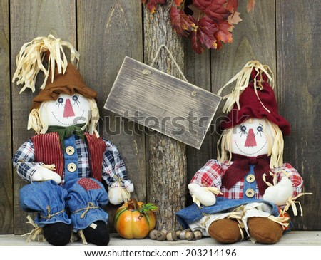Blank rustic sign hanging on tree with boy and girl scarecrows