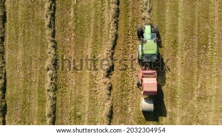 hay cutting and harvesting with hay baling in summer Royalty-Free Stock Photo #2032304954