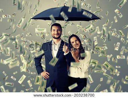 smiley successful couple with umbrella standing under money rain