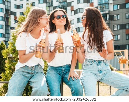 Three young beautiful smiling hipster female in trendy summer same clothes.Sexy carefree women posing in the street.Positive models having fun in sunglasses. Drinking bottle beer. Oktoberfest Royalty-Free Stock Photo #2032426592