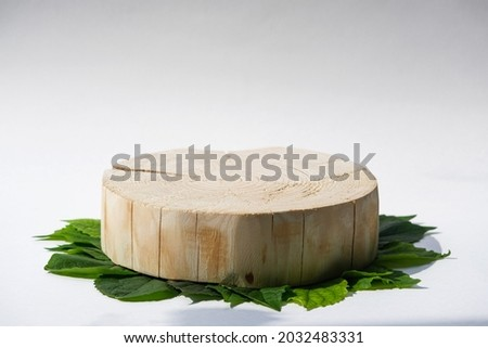 one round cut wooden platform on green leaves background, geometric podium, pedestal, mock up, eco scene for presentation of beauty products Royalty-Free Stock Photo #2032483331
