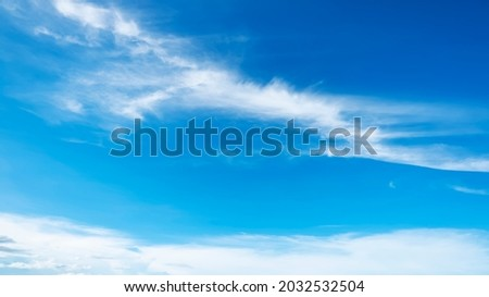 The sky has the light of the sun, the sky is blue, there are small and large clouds alternating and moving slowly, with the sunlight passing, creating a miraculous abstract shape, a hot day. Royalty-Free Stock Photo #2032532504