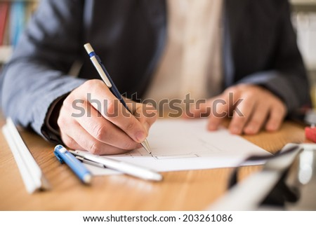 Architect working at his desk drawing a sketch. #203261086