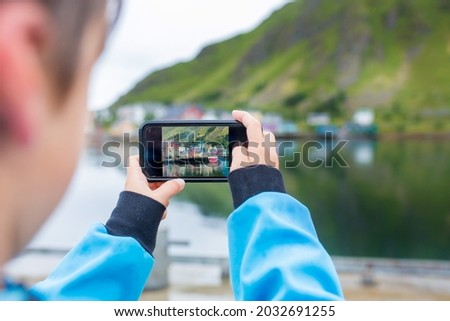 Cute child, boy, taking picture of the typical Rourbuer fishing cabins in Lofoten village on a rainy day, summertime. Traditional norwegian wooden house rorbuer