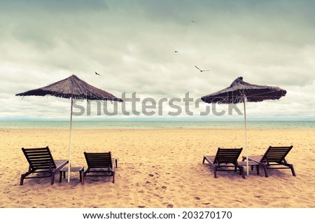 Sunbeds and umbrellas on empty sandy beach. Instagram toned photo #203270170