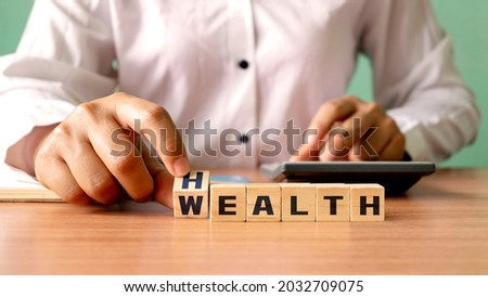 Young woman hand turning wooden dice with wealth and health, financial wealth concept. Investing in life and health insurance Royalty-Free Stock Photo #2032709075