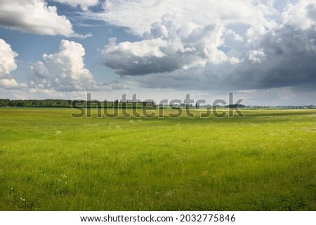 Green hills of a plowed agricultural field and forest. Idyllic summer rural scene. Dramatic sky, rain, thunderstorm. Pure nature, environnement, farm, countryside living, ecotourism. Panoramic view Royalty-Free Stock Photo #2032775846