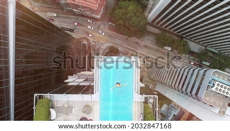 AERIAL. Top view of Hong Kong streets from the drone. And woman at the sweeming pool. Royalty-Free Stock Photo #2032847168