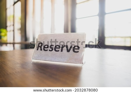 Reserve text white plate on the wooden table in the restaurants or cafe, booked Royalty-Free Stock Photo #2032878080
