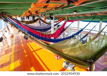 Colorful hammocks on Amazon Rainforest wooden boat in sunny summer day. Alter do Chão, Para, Brazil. Concept of nature, conservation, environment, ecology, vacation, tourism, travel.