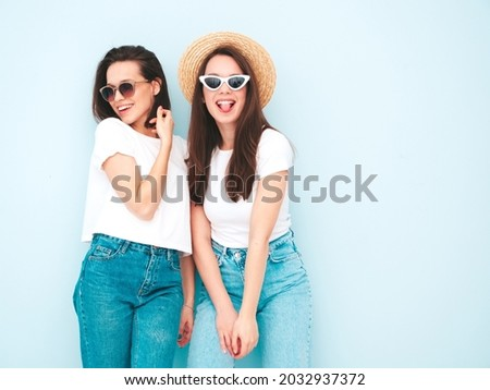 Two young beautiful smiling hipster female in trendy summer white t-shirt and jeans clothes.Sexy carefree women posing near light blue wall in studio.Positive and cheerful models in hats. Shows tongue Royalty-Free Stock Photo #2032937372
