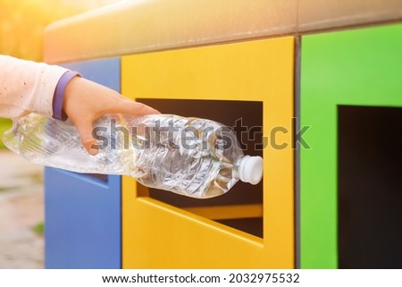 Close up hand throwing plastic bottle recycling container garbage sorting rubbish collection bin. Hand kid put bottle plastic trash can. Reduce waste recycle bins. Garbage recycling plastic trash bins Royalty-Free Stock Photo #2032975532