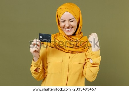 Overjoyed fun successful young arabian asian muslim woman in abaya hijab yellow clothes hold credit bank card do winner gesture isolated on olive green background. People uae islam religious concept. Royalty-Free Stock Photo #2033493467