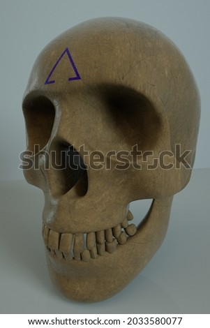 Human skull with an symbol on the forehead.