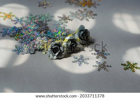 Glittery snowflakes with gray artificial roses on a gray background. A scattering of multicolored sparkly decorative snowflakes.  Selective focus. Royalty-Free Stock Photo #2033711378