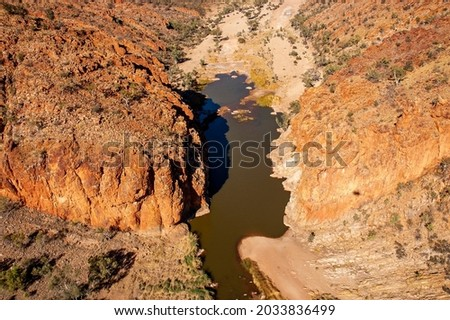 Spectacular Glen Helen Gorge at the western end of the West MacDonnell Ranges in Central Australia, seen from the air.  The permanent waterhole here is fed by the Finke River.  Royalty-Free Stock Photo #2033836499