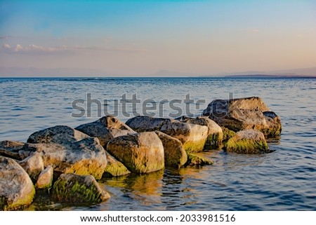 Stone path to the sea. Beautiful seascape with large stones on the sea. Blue sea and a pile of stones Royalty-Free Stock Photo #2033981516
