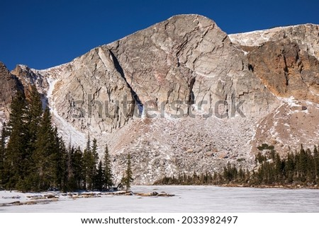 The Snowy Range of southwestern Wyoming in early winter. Medicine Bow-Routt National Park. Snowy Range in Wyoming's Medicine Bow Wilderness.  Boulders, trees, snow and sheer rock faces. Royalty-Free Stock Photo #2033982497