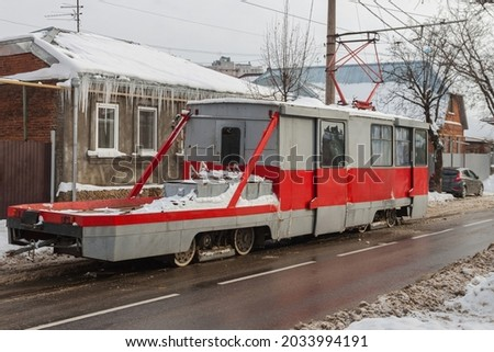 Old red-gray repair streetcar KTM-5M3. Gray winter cityscape Royalty-Free Stock Photo #2033994191