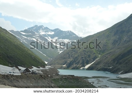A scenic picture of valley with Mountains surrounding a small lake, Glacier and clouds in the sky. nature photography. tourism Pakistan. travel.