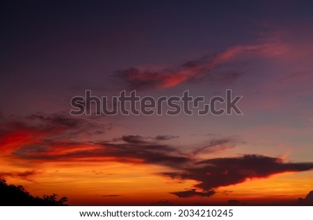 Dramatic red and orange sky and clouds abstract background. Red-orange clouds on sunset sky. Warm weather background. Art picture of the sky at dusk. Sunset abstract background. Dusk and dawn concept.