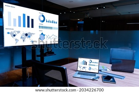 Mock up sales summary slide show presentation on display television and laptop with notebook on table in meeting room