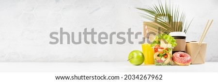 Summer take away food banner - set with drinks, coffee cup, orange juice, shrimp salad, noodles, donut, packet in white interior, palm leaf. Advertising for restaurant menu, delivery food service. Royalty-Free Stock Photo #2034267962