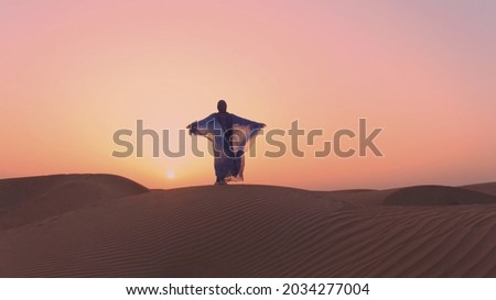 Arabic woman weared in traditional UAE dress - abayain rising her hands on the sunset at a desert. Royalty-Free Stock Photo #2034277004