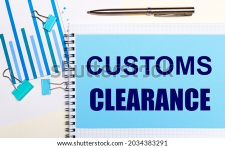 On a light background - light blue diagrams, paper clips and a sheet of paper with the text CUSTOMS CLEARANCE. View from above. Business concept