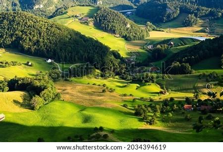 A village in a green mountain valley. Mountain green valley village panorama. Village in mountains. Mountain green hills village Royalty-Free Stock Photo #2034394619