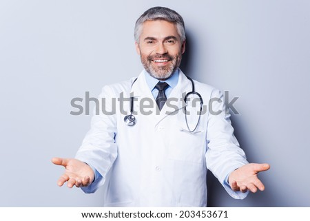 Cheerful doctor. Cheerful mature grey hair doctor looking at camera while stretching out hands and smiling while standing against grey background #203453671