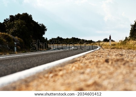 Scenic view on the gravel road with stones and vegetation on roadsides, selective focus. High quality photo Royalty-Free Stock Photo #2034601412