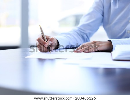 Businesswoman sitting at office desk signing a contract with shallow focus on signature #203485126