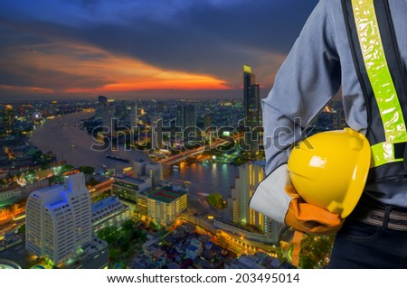 Engineer holding a yellow helmet for the safety of workers with high buildings along the river as a backdrop in the business district at dusk. #203495014