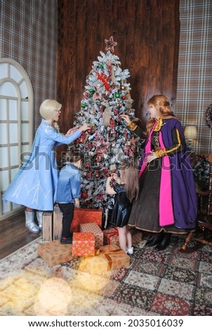 Fairy-tale princesses in costumes of Anna and Elsa with children