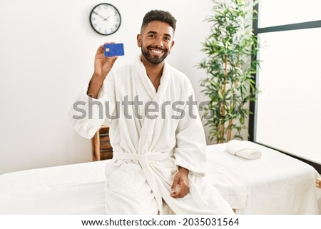 Young african american holding credit card at beauty center.