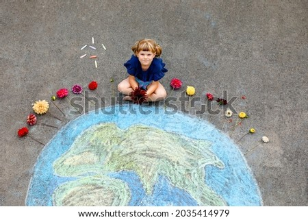 Little preschool girl with flowers and earth globe painting with colorful chalks on ground. Positive toddler child. Happy earth day concept. Creation of children for saving world, environment and Royalty-Free Stock Photo #2035414979