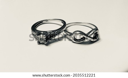 Two women's rings resting on each other. One with the forever symbol.