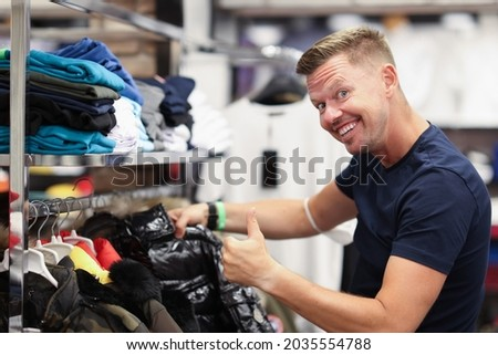 Young man choosing outerwear and showing thumb up in store Royalty-Free Stock Photo #2035554788