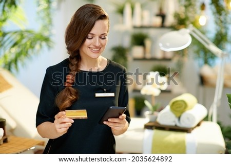 smiling 40 years old woman employee with smartphone and credit card making online purchases on e-commerce website in modern beauty salon.