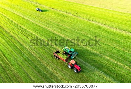 Forage harvester during grass cutting for silage in field. Harvesting biomass crop. Self-propelled Harvester for agriculture industry. Tractor work on silage season. Farm equipment and farming machine Royalty-Free Stock Photo #2035708877
