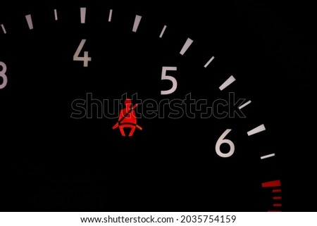 Seat belt warning light on vehicle dashboard. Safety restraint law, violation and travel safety concept Royalty-Free Stock Photo #2035754159