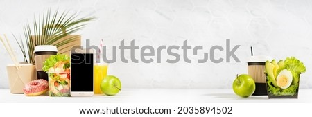 Take away food banner - set of drinks, coffee, salads with shrimp, vegetables, noodles, donut, packet in white interior, palm leaf. Mockup advertising for delivery service, restaurant, online order. Royalty-Free Stock Photo #2035894502