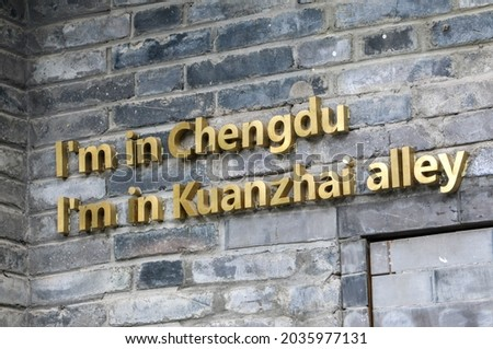 Gold sign saying 'I'm in Chengdu, I'm in Kuanzhai Alley' on brick wall at the the famous Kuanzhai Alley (Wide and Narrow Alleys) in Chengdu, Sichuan, China - three parallel ancient city alleys Royalty-Free Stock Photo #2035977131