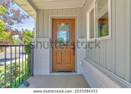 Front wooden door exterior with ornate glass panel and digital entry access with keypad Royalty-Free Stock Photo #2035984355
