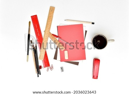 School supplies or cartoons or office supplies spread out on a white table with a cup of coffee