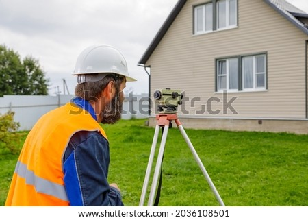 A male engineer works with the optical level on site. A builder in a helmet looks into an optical device. Royalty-Free Stock Photo #2036108501